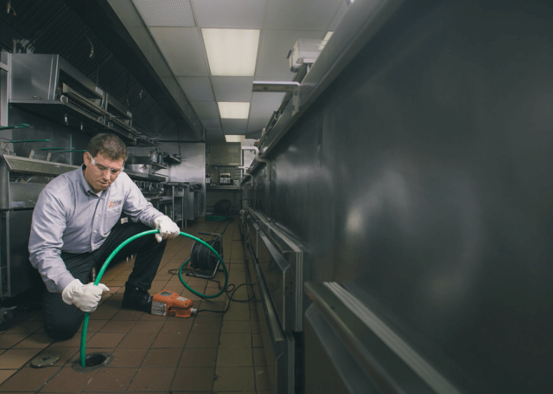 A Zoom Drain specialist holds a hose down a commercial kitchen drain