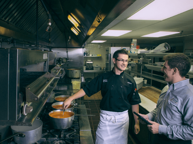 A Zoom Drain technician talks to a cook stirring a pot in a commercial kitchen